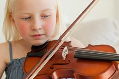 A girl plays the violin and looks at the strings while she does, Stock Photos