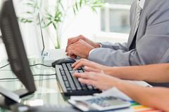 Business people tapping together on computers Stock Photos