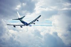 Airliner flying through the thick clouds Stock Photos