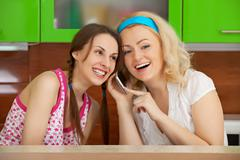 two friends on kitchen get a phone call - stock photo