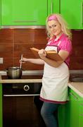 blonde reading a book and preparing food on kitchen - stock photo