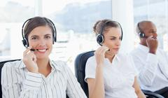 Stock Photo of Smiling telephone hotline employee sitting next to her colleagues