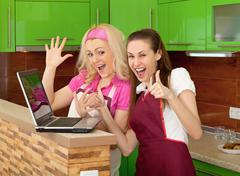 Happy friends on kitchen with a laptop Stock Photos