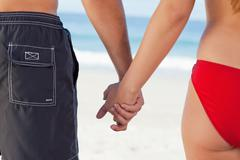 Young couple standing upright while holding their hands Stock Photos