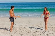 Tanned couple playing with beach racket Stock Photos