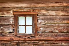 small window in the old wooden wall - stock photo