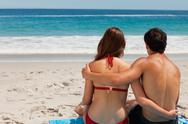 Rear view of a young tanned couple sitting on beach towel Stock Photos