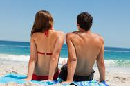 Rear view of a tanned couple sitting on a beach towel Stock Photos