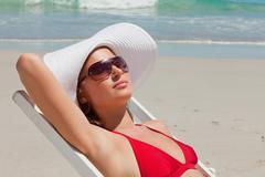 Pretty woman on a deck chair with sunglasses having a sunbath Stock Photos