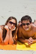 Portrait of a couple being tanning on the beach Stock Photos
