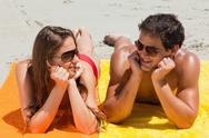 Close-up of a tanned couple lying on the beach Stock Photos