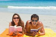Portrait of a tanned couple reading a book on the beach Stock Photos