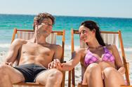 Couple smiling in deck chairs Stock Photos
