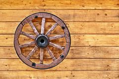Old wagon wheel on a wooden wall Stock Photos