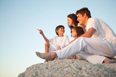 Family sitting on a natural stone wall together as the son points in front of Stock Photos