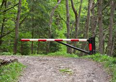 Barrier, blocking the road into the woods Stock Photos
