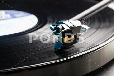 Stock photo of vinyl analog record player cartridge and lp