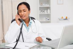 Serious doctor talking on the phone while sitting at her desk - stock photo