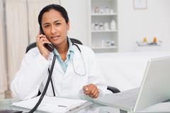 Serious doctor looking at the camera while talking on the phone - stock photo