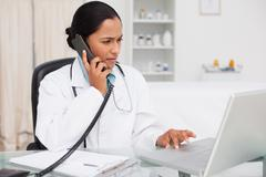 Serious doctor using her laptop while talking on the phone - stock photo