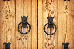Handles on the old-fashioned wooden door Stock Photos