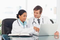 Serious doctor pointing at the screen of the laptop while talking to her - stock photo