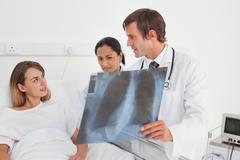 Serious doctor talking to a patient about her chest x-ray - stock photo