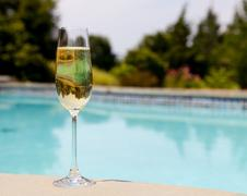 flute of cold champagne by side of pool - stock photo
