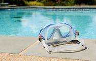 Swimming mask by side of blue pool Stock Photos