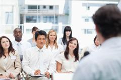 Business team looking ahead as they watch their colleague giving a speech Stock Photos