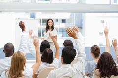 Audience raising their arms while watching a businesswoman - stock photo