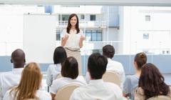 Businesswoman gesturing towards an audience during a presentation - stock photo