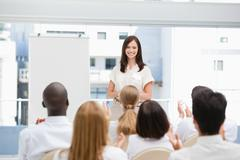 Woman looking at an audience as they are applauding her - stock photo