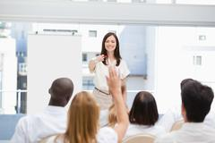 Woman pointing to a member of the audience who has her arm raised - stock photo