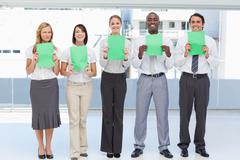 Business team holding green sheets in front of them Stock Photos