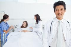 Doctor looking ahead while his colleagues treat a patient - stock photo