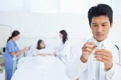 Stock Photo of Doctor preparing a syringe while his colleagues are treating a patient