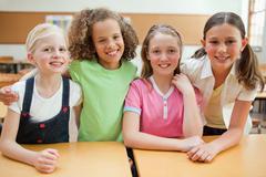 Smiling schoolgirls together behind desk Stock Photos