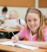 Young female schoolchild sitting at her desk Stock Photos