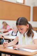 Primary student working on exercise book - stock photo