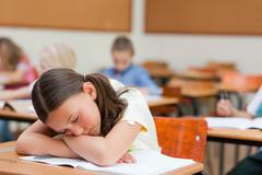 Primary student felt asleep at desk during class - stock photo