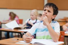 Primary student sitting at desk thinking - stock photo