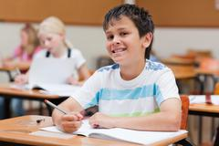 Smiling primary student sitting at desk - stock photo