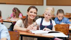 Smiling primary teacher helping student - stock photo