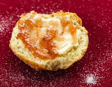 half scone with butter and jam on red tablecloth - stock photo