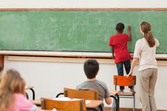 Boy standing on chair to reach blackboard - stock photo