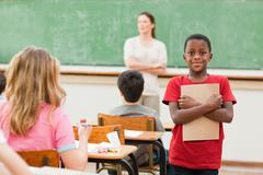Student standing in class with his exercise book - stock photo