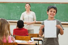 Stock Photo of Smiling boy showing his test results