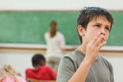 Boy acting cool in class - stock photo