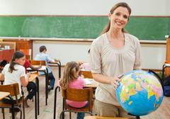 Smiling teacher holding globe - stock photo